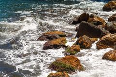 Stones on the beach about which the waves are beating royalty free stock photo