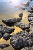 Stones beautifully illuminated by the sun in the water. Texture Royalty Free Stock Photography