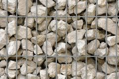 Stones behind a net. Of containment road Stock Photos
