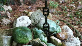 Stones and black old ship's chain spring rain. The stones are covered with green moss and black old ship's chain spring rain stock video footage