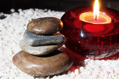 Stones and blazing candle Stock Photography