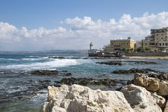 Stones and blue ocean at the coast of Tyre with lighthouse in Tyre, Sour, Lebanon Royalty Free Stock Photo