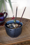 Stones in Bowl. Glazed bowl with stones immersed in water as a metaphoric meditation on essential elements in a spa setting Stock Photo