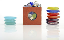 Stones and Box. Stones: first pile on left, three pale blue or aqua flat stones in stack, then brown box stacked with glass balls or stones in many colors, and Royalty Free Stock Images