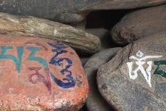 Stones with the Buddhist mantra written in Sanskrit Om Mani Padmehum. Stock Photos