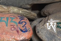 Stones with the Buddhist mantra written in Sanskrit Om Mani Padmehum. Royalty Free Stock Photos