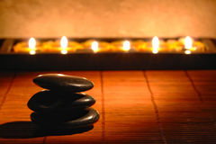 Stones Cairn and Candles for Quiet Zen Meditation. Polished black stones Zen inspiration cairn with row of soft burning candles on bamboo mat for a soft stock image
