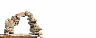 Stone arch isolated on white background. Stones cairn formed an arch isolated on white background with empty space Royalty Free Stock Images