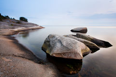 Stones in calm sea. Calm sea by the coastline of Karlshamn, Sweden royalty free stock photos
