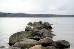 Stones in calm water, in the distance a green hill. Rocks in a lake, cloudy sky and text space Royalty Free Stock Photos