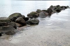 Stones in calm water. Rocks in a lake or sea and text space Royalty Free Stock Image