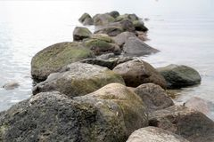 Stones in calm water. Rocks in a lake or sea and text space Royalty Free Stock Photography