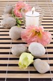 Stones with candle on bamboo mate Royalty Free Stock Photo