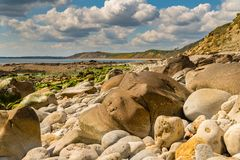 Osmington Bay, Jurassic Coast, Dorset, UK. Stones and clouds at Osmington Bay, Osmington Mills, near Weymouth, Jurassic Coast, Dorset, UK Stock Images