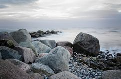Stones on the coast in the sea, soft waves by long time exposure, copy space. Rough stones on the coast in the sea with soft waves by long time exposure, copy royalty free stock photos