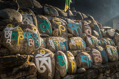 Stones with colorful nepalese characters. Nepalese symbols carved on the stones Stock Image