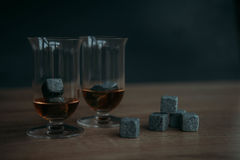 Stones for cooling whiskey and glases tulup on dark wooden background. Grey stones cubes for cooling whiskey and glases tulip on dark wooden background Stock Photo