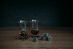 Stones for cooling whiskey and glases tulup on dark wooden background. Grey stones cubes for cooling whiskey and glases tulip on dark wooden background Stock Image