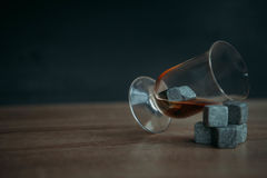 Stones for cooling whiskey and glases tulup on dark wooden background. Grey stones cubes for cooling whiskey and glases tulip on dark wooden background Royalty Free Stock Images