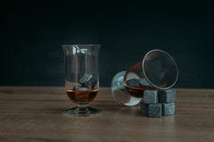 Stones for cooling whiskey and glases tulup on dark wooden background. Grey stones cubes for cooling whiskey and glases tulip on dark wooden background Royalty Free Stock Photography