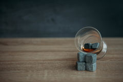 Stones for cooling whiskey and glases tulup on dark wooden background. Grey stones cubes for cooling whiskey and glases tulip on dark wooden background Stock Images