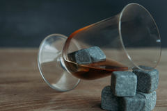 Stones for cooling whiskey and glases tulup on dark wooden background. Grey stones cubes for cooling whiskey and glases tulip on dark wooden background Royalty Free Stock Photos