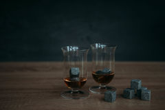 Stones for cooling whiskey and glases tulup on dark wooden background. Grey stones cubes for cooling whiskey and glases tulip on dark wooden background Royalty Free Stock Image
