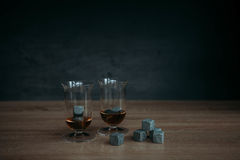 Stones for cooling whiskey and glases tulup on dark wooden background. Grey stones cubes for cooling whiskey and glases tulip on dark wooden background Stock Photography