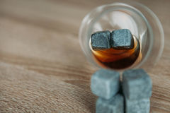 Stones for cooling whiskey and glases tulup on dark wooden background. Grey stones cubes for cooling whiskey and glases tulip on dark wooden background Stock Photos