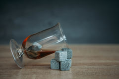 Stones for cooling whiskey and glases tulup on gark wooden background. Grey stones cubes for cooling whiskey and glases tulip on gark wooden background Stock Image
