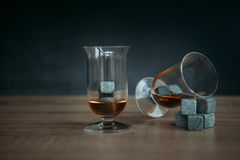 Stones for cooling whiskey and glases tulup on gark wooden background. Grey stones cubes for cooling whiskey and glases tulip on gark wooden background Royalty Free Stock Photo