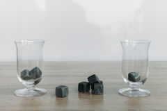 Stones for cooling whiskey and glases tulup on light wooden background. Grey stones cubes for cooling whiskey and glases tulip on light wooden background Royalty Free Stock Photography