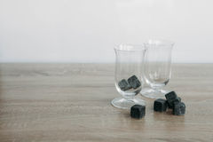 Stones for cooling whiskey and glases tulup on light wooden background. Grey stones cubes for cooling whiskey and glases tulip on light wooden background Stock Images