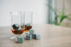 Stones for cooling whiskey and glases tulup on light wooden background. Grey stones cubes for cooling whiskey and glases tulip on light wooden background Stock Photography