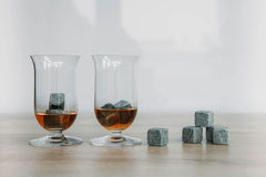 Stones for cooling whiskey and glases tulup on light wooden background. Grey stones cubes for cooling whiskey and glases tulip on light wooden background Royalty Free Stock Photo