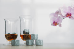 Stones for cooling whiskey and glases tulup on light wooden background. Grey stones cubes for cooling whiskey and glases tulip on light wooden background Royalty Free Stock Images