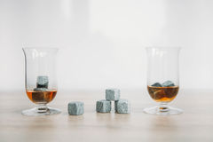 Stones for cooling whiskey and glases tulup on light wooden background. Grey stones cubes for cooling whiskey and glases tulip on light wooden background Stock Photo