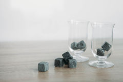 Stones for cooling whiskey and glases tulup on light wooden background. Grey stones cubes for cooling whiskey and glases tulip on light wooden background Royalty Free Stock Image