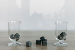 Stones for cooling whiskey and glases tulup on light wooden background. Grey stones cubes for cooling whiskey and glases tulip on light wooden background Royalty Free Stock Photos