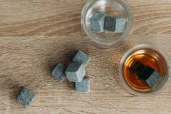 Stones for cooling whiskey and glases tulup on light wooden background. Grey stones cubes for cooling whiskey and glases tulip on light wooden background Stock Image