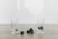 Stones for cooling whiskey and glases tulup on light wooden background. Grey stones cubes for cooling whiskey and glases tulip on light wooden background Stock Photos