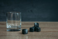 Stones for cooling whiskey and glases tumbler on dark wooden background Stock Images
