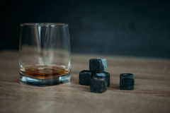 Stones for cooling whiskey and glases tumbler on dark wooden background Stock Image