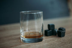 Stones for cooling whiskey and glases tumbler on dark wooden background Royalty Free Stock Photo
