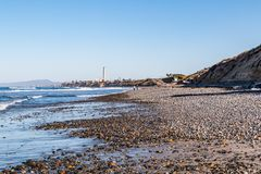 Stones Cover South Carlsbad State Beach with Power Station Landmark Tower. Stones cover South Carlsbad State Beach in San Diego, California, with a power station stock image