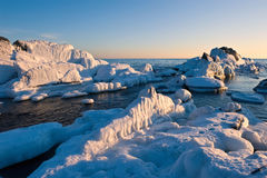Stones covered with ice on the beach. Royalty Free Stock Photography