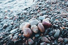 Stones of different shades and different oval shapes lie on the stony shore of a large and cold lake. Stock Photography