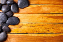 Stones with drops in the top left corner on wooden Royalty Free Stock Photos