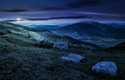 Stones on the edge of mountain hillside at night. Huge stones among the grass on top of the hillside meadow near the edge of a mountain. vivid summer landscape Royalty Free Stock Images