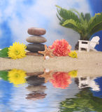 Stones and Flowers on Beach. Balanced Stones and Flowers with Sea Shells on Beach With Chair and Palm Tree in Background Royalty Free Stock Photography